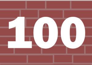 Liczba 100 na tle murku